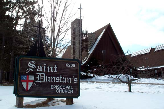 St. Dunstan's Episcopal Church, 6205 University Ave., Madison, Wis., with snowcovered ground and wooden sign in foreground.