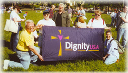 picture of Dignity members in grassy field holding banner with DignityUSA logo