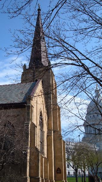 Grace Episcopal Church's historic steeple, seen with the Wisconsin State Capitol Building in the background.